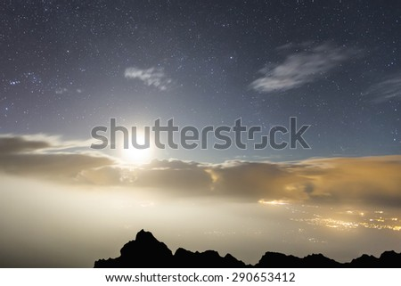 The moon light illuminating an island as seen from above the clouds in Maui, Hawaii. Glowing clouds and city lights in the distance.  - stock photo
