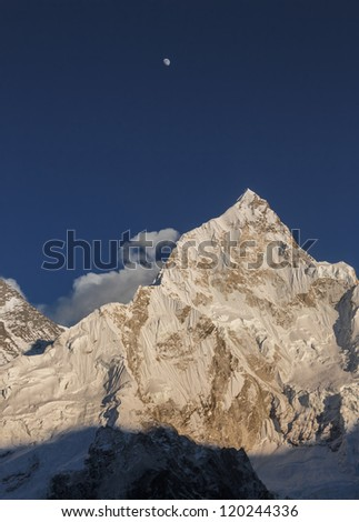 The Moon, Nuptse (7864 m), and slope of the Mt. Everest (8848 m) in the evening (view from Kala Patthar) - Nepal, Himalayas - stock photo