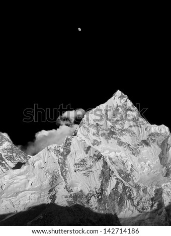 The Moon, Nuptse (7864 m), and slope of the Mt. Everest (8848 m) in the evening (view from Kala Patthar) - Nepal, Himalayas (black and white) - stock photo
