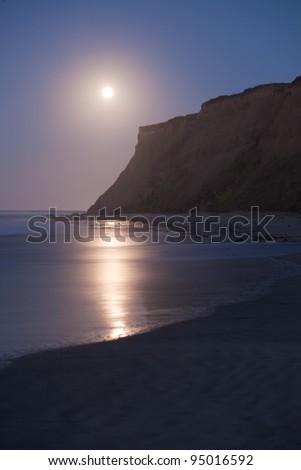 The moon setting at sunrise at Half Moon Bay, California - stock photo