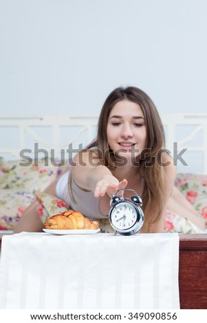 The morning and breakfast of young beautiful girl in bed with the clock service at home - stock photo