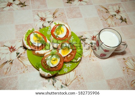 The morning breakfast sandwich, sandwich of toast green leaf lettuce, tomatoes and chicken boiled eggs with dill. Near kefir Takane. - stock photo