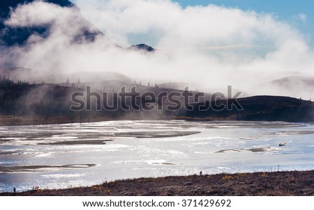 The morning sun backlights the misty mountains - stock photo