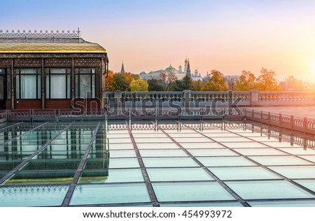 The Moscow Kremlin is visible over the tops of autumn trees and squares glass pavilion
