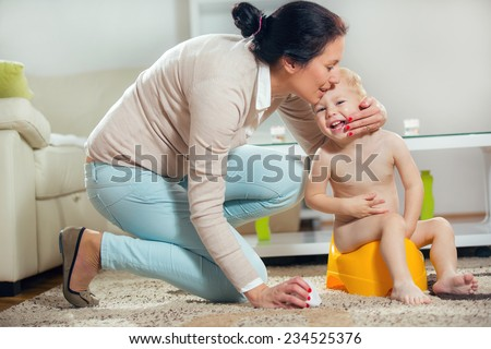 The mother and her child to sit on the potty - stock photo