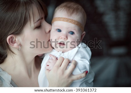 The mother holds the baby and kisses her on the cheek. - stock photo