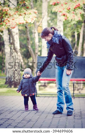 The mother holds the baby by the hand on a walk, cool weather, vertical. - stock photo