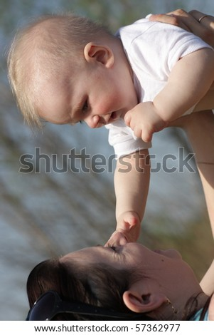 The mother tosses up her baby outdoor - stock photo