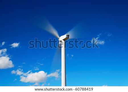 The motion of a wind turbine against blue sky - stock photo
