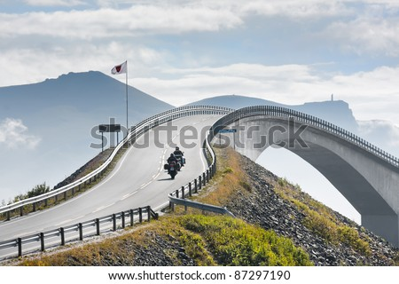 The motorcyclists rising on the abrupt bridge through fjord on the Atlantic road in cloudy weather, Norway - stock photo