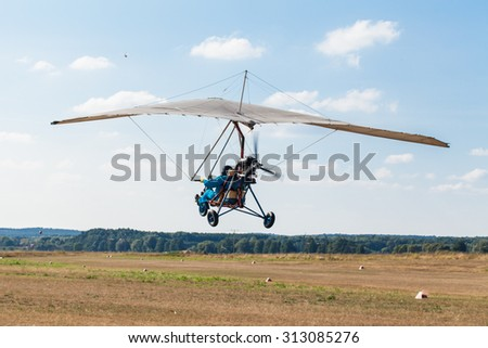 The motorized hang glider in the blue sky - stock photo