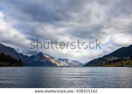 The mountain and the lake is under the cloudy sky