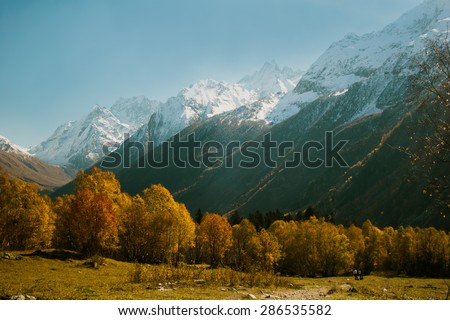 The mountain autumn landscape with colorful forest and high peaks Caucasus Mountains - stock photo