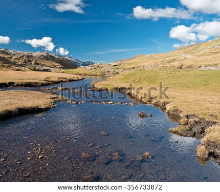 The mountain stream is flowing on the plateau in the cirque of Troumouse. - stock photo
