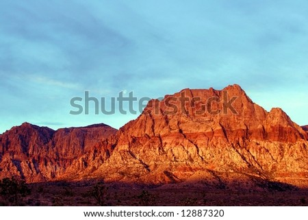 The mountains glow fiery red at sunrise in Red Rock Canyon Las Vegas Nevada.
