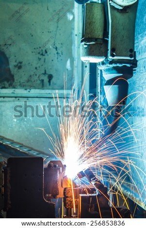The movement of the welding robot in a car factory - stock photo