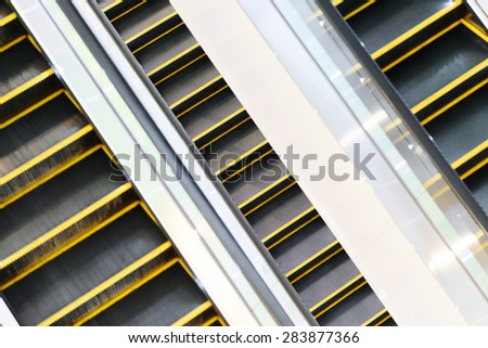 The multiple steps and directions of an escalator in the modern shopping mall - stock photo