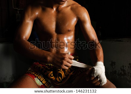 The muscular fighter tying tape around his hand preparing to fight - stock photo
