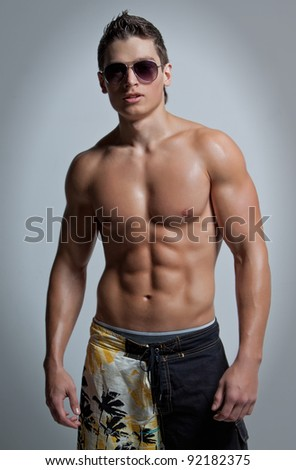 The muscular young naked smiling sexy boy in the beach shorts and sunglasses - stock photo