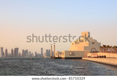 The Museum of Islamic Art in Doha, Qatar, at sunset with the emerging high-rise skyline behind it - stock photo
