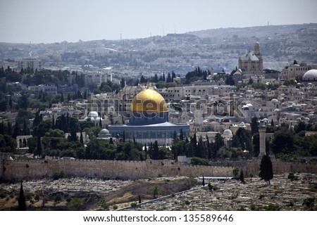 The Muslim Dome of the Rock behind the old Jerusalem surrounding city wall ass seen from Mount of the Olives. Israel. - stock photo
