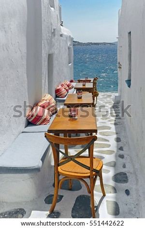 The narrow path to the sea with furniture at Mykonos island in Greece