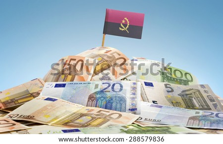 The national flag of Angola sticking in a pile of mixed european banknotes.(series) - stock photo