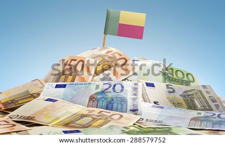 The national flag of Benin sticking in a pile of mixed european banknotes.(series) - stock photo