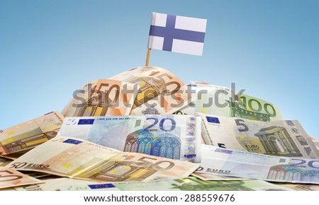 The national flag of Finland sticking in a pile of mixed european banknotes.(series) - stock photo