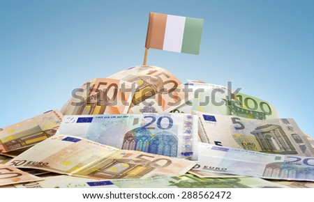 The national flag of Ivory Coast sticking in a pile of mixed european banknotes.(series) - stock photo