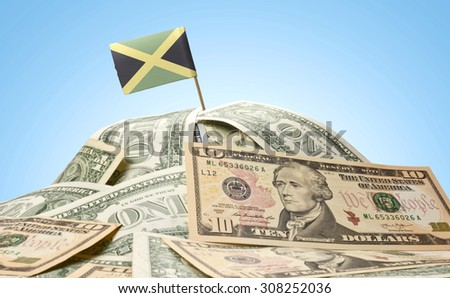 The national flag of Jamaica sticking in a pile of american dollars.(series) - stock photo