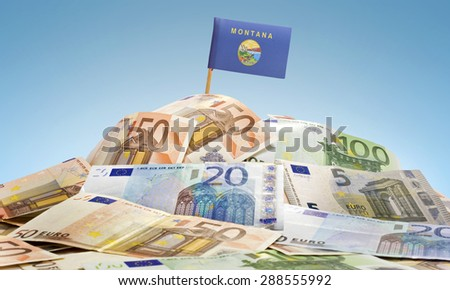 The national flag of Montana sticking in a pile of mixed european banknotes.(series) - stock photo