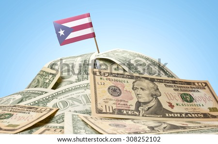 The national flag of Puerto Rico sticking in a pile of american dollars.(series) - stock photo