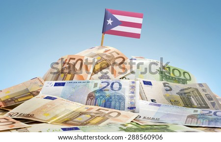The national flag of Puerto Rico sticking in a pile of mixed european banknotes.(series) - stock photo