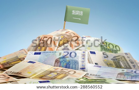 The national flag of Saudi Arabia sticking in a pile of mixed european banknotes.(series) - stock photo