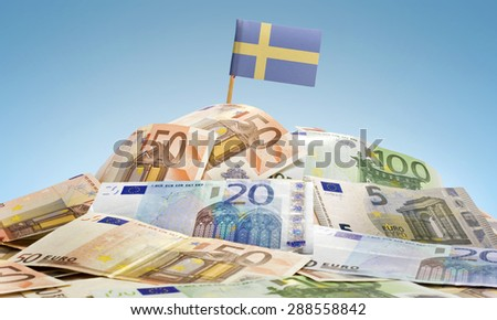 The national flag of Sweden sticking in a pile of mixed european banknotes.(series) - stock photo