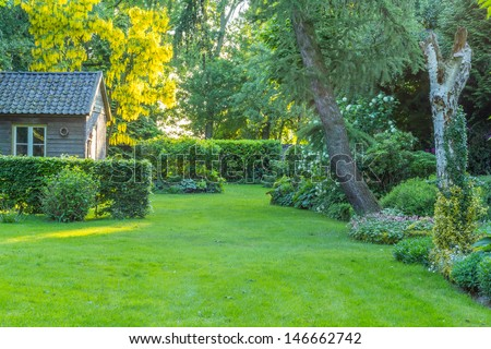 The neat garden at sunset - stock photo