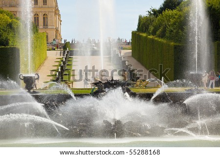 The Neptune fountain spraying water in Versailles Chateau. Unrecognizable people. France series - stock photo