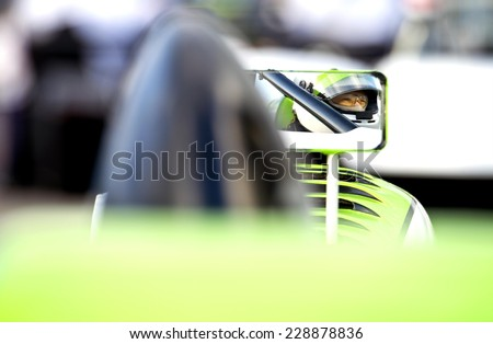 The nervous, tencely concentrated look in the eyes of a race car driver in his car on the starting grid of a race track, reflected in the side mirror of his vehicle. - stock photo