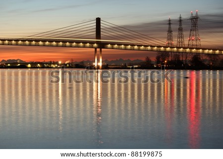 The new Canada Line, a rapid transit commuter train, crosses the Fraser River from Richmond and the airport into Vancouver. British Columbia, Canada. - stock photo