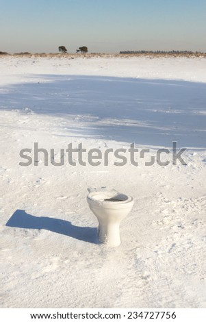 The New Forest bathroom facilities are a little behind the times. A WC sits in the snow in the middle of the Forest - stock photo