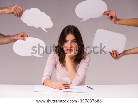 The new idea. Girl sits at a table at the head of the new ideas in the form of empty bubble for text, isolated on a gray background - stock photo