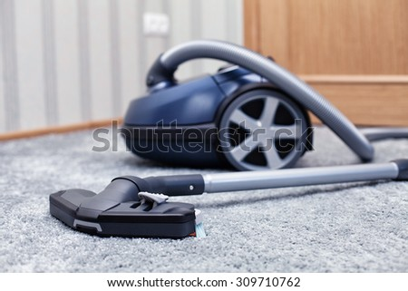 The new vacuum cleaner lies in a room - stock photo