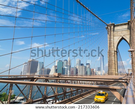 The New York City Skyline from Brooklyn Bridge with a typical Yellow Taxi on the bridge - stock photo