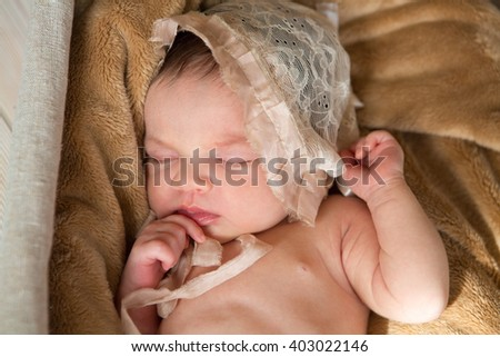 the newborn child in a cap sleeps on a blanket