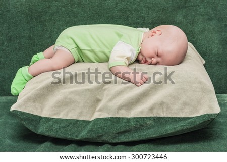 The newborn one-month baby lies on a big pillow and sleeps