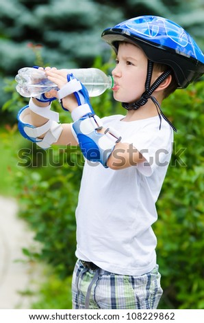 The nice boy skater drinking water from a bottle - stock photo