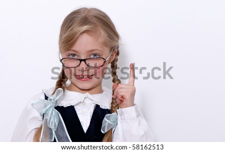 The nice schoolgirl in glasses on a light background - stock photo