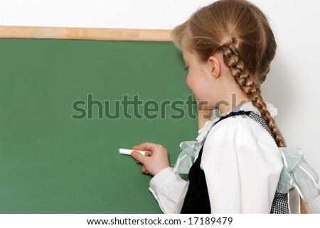 The nice schoolgirl near to a school board - stock photo