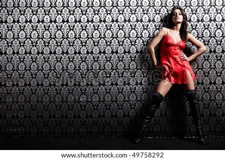 The nice young girl in the red costs at a wall - stock photo